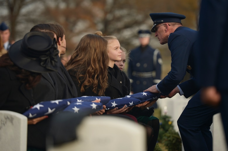 Maj. Gen. Scott Vander Hamm, the Air Force assistant deputy chief of staff of operations, presents a flag to Annalise during the interment for her father, Maj. Troy Gilbert, at Arlington National Cemetery, Va., Dec. 19, 2016.  He is survived by his mother and father, Kaye and retired Senior Master Sgt. Ron Gilbert; sister, Rhonda Jimmerson; wife, Ginger Gilbert Ravella; sons, Boston and Greyson; and daughters, Isabella, Aspen and Annalise. (U.S. Air Force photo/ Tech. Sgt. Joshua DeMotts)