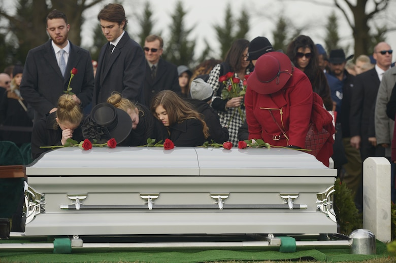 Maj. Troy Gilbert's family places roses on his casket during his interment at Arlington National Cemetery, Va., Dec. 19, 2016. Gilbert was killed Nov. 27, 2006, while flying a mission in direct support of coalition ground combat operations when his F-16C Fighting Falcon crashed approximately 20 miles northwest of Baghdad. This was the third interment for the Airman at Arlington since 2006, and reunited remains recovered this year with partial remains originally recovered in 2006 and 2012. (U.S. Air Force photo/ Tech. Sgt. Joshua DeMotts)