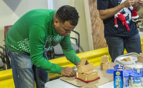 U.S. Marine Gunnery Sgt. Abraham Gonzalez, career planner, I Marine Expeditionary Force Headquarters Group, constructs a gingerbread house during the I MHG Holiday Party at Marine Corps Base Camp Pendleton, Calif., Dec. 14, 2016. The Marines and their family members celebrated the holiday season by building gingerbread houses, decorating stockings and designing Christmas ornaments while enjoying a holiday meal in camaraderie. (U.S. Marine Corps photo by Cpl. Alvin Pujols)
