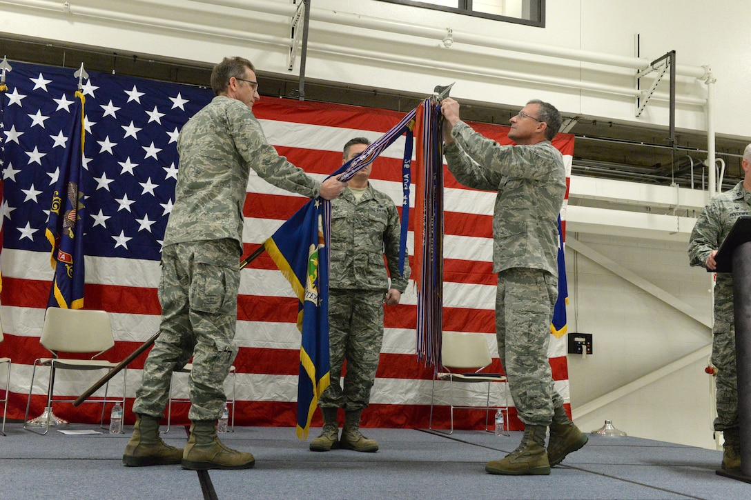 Brig. Gen. Robert Becklund, the North Dakota deputy adjutant general, right, attaches a streamer, representing the Air Force Outstanding Unit Award, onto the 119th Wing guidon, as Col. Kent Olson, the 119th Wing commander, lowers the unit flag during a recognition ceremony at the as Chief Master Sgt. Duane Kangas, the 119th Wing command chief master sergeant, center, looks on at the North Dakota Air National Guard Base, Fargo, North Dakota, Dec. 3, 2016. (U.S. Air National Guard photo by Senior Master Sgt. David H. Lipp/Released)