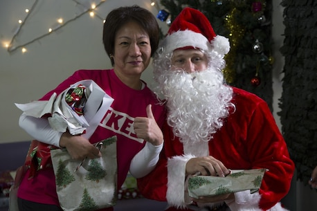 A caregiver poses for a photo with Santa Claus during a Christmas visit at the Reimei no Sato home for the disabled Dec. 16 in Ishikawa, Okinawa, Japan. Reimei no Sato provides care for adults with special day-to-day living needs. During the visit, Marines from Camp Hansen delivered Christmas gifts provided by the Marine Officers Spouses Club and spent time spreading Christmas cheer with the residents. The Marines are with 12th Marine Regiment, 3rd Marine Division, III Marine Expeditionary Force. (U.S. Marine Corps photo by Cpl. Janessa K. Pon)