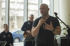 """U.S. Army Sgt. Andrew Bell, National Intrepid Center of Excellence patient, speaks to the audience before a performance at Walter Reed National Military Medical Center in Bethesda, Md., Dec. 13, 2016.  U.S. Air Force Band Max Impact accompanied Bell as he performed """"The Christmas Song"""" at the NICoE Creative Arts Café. NCAC is performance platform for NICoE patients and staff to share creativity though creative arts once a month. (U.S. Air Force photo by Airman 1st Class Rustie Kramer)"""