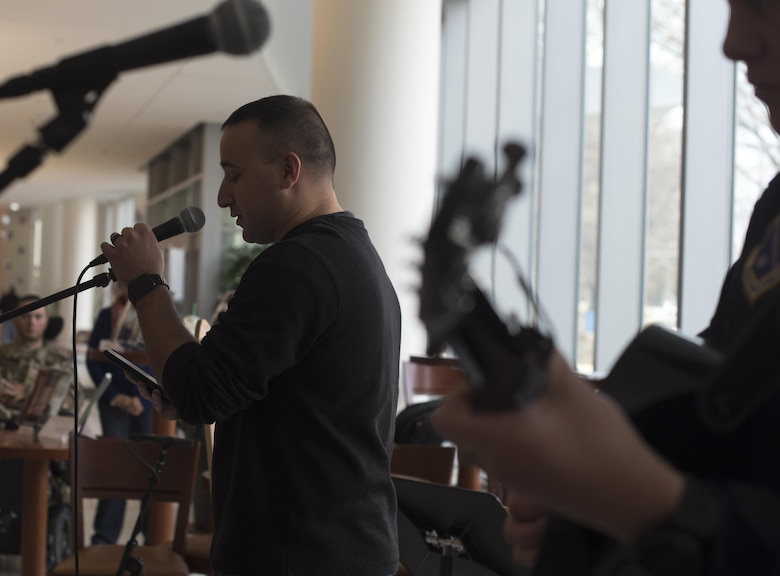 """Marine Staff Sgt. Anthony Mannino, National Intrepid Center of Excellence patient, performs a spoken word piece at NICoE Creative Arts Café at Walter Reed National Military Medical Center in Bethesda, Md., Dec. 13, 2016. U.S. Air Force Band's Max Impact accompanied Mannino spoken word piece with music from King's of Leon's song """"Walls."""" NCAC is performance platform for NICoE patients and staff to share creativity though creative arts once a month. (U.S. Air Force photo by Airman 1st Class Rustie Kramer)"""