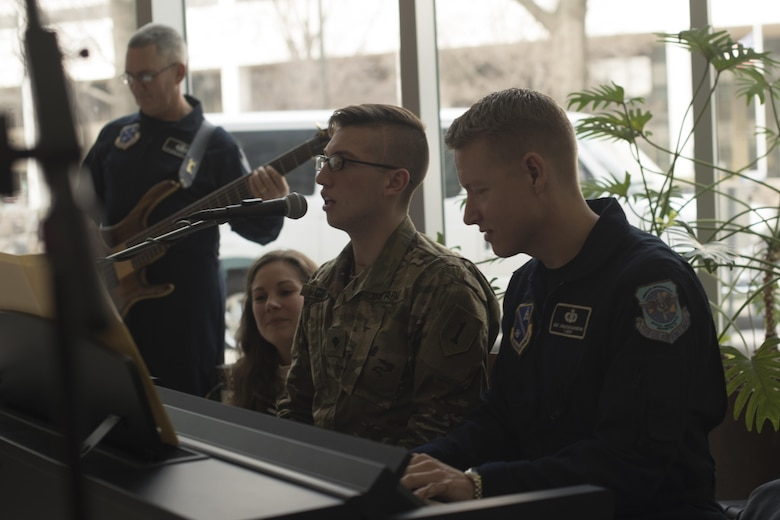 """U.S. Army Specialist Tyler McGibbon, National Intrepid Center of Excellence patient, and U.S. Air Force Master Sgt. Jonathon McPherson, U.S Air Force Bann Max Impact keyboard player, perform """"The Messenger"""" by Linkin Park at NICoE Creative Arts Café at Walter Reed National Military Medical Center in Bethesda, Md., Dec. 13, 2016. NCAC is performance platform for NICoE patients and staff to share creativity though creative arts once a month. NCAC began as a collaboration between the U.S. Air Force Band and NICoE music therapy program October 2016.  (U.S. Air Force photo by Airman 1st Class Rustie Kramer)"""