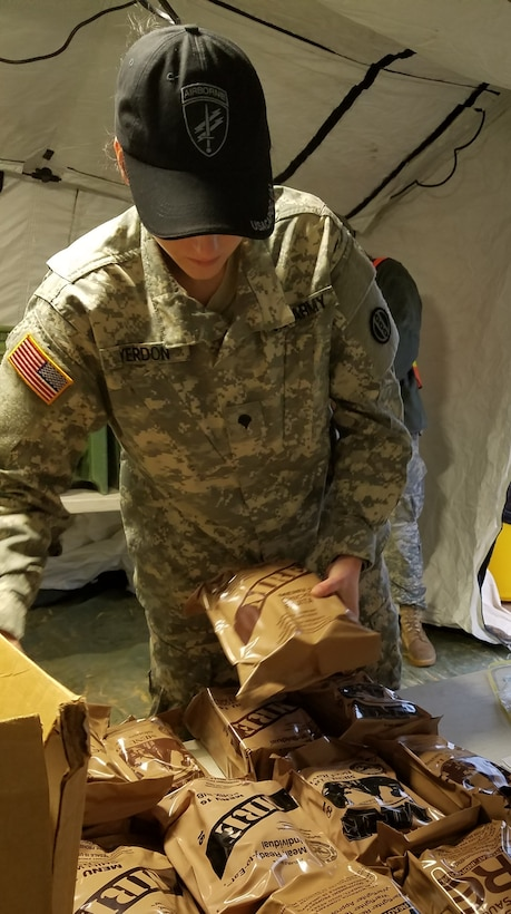 Spc. Savannah Yerdon, a culinary specialist assigned to the 1018th Quartermaster Company in Schenectady, N.Y., stacked MREs on a table prior to Soldiers filing into the DFAC tent for breakfast at Fort Bragg, N.C., Luzon Drop Zone on 12 Dec., 2016. Yerdon was part of a six person food service crew who provided meal rations for hundreds of Soldiers during Operation Toy Drop XIX. (U.S. Army photo by Capt. Ebony Malloy)