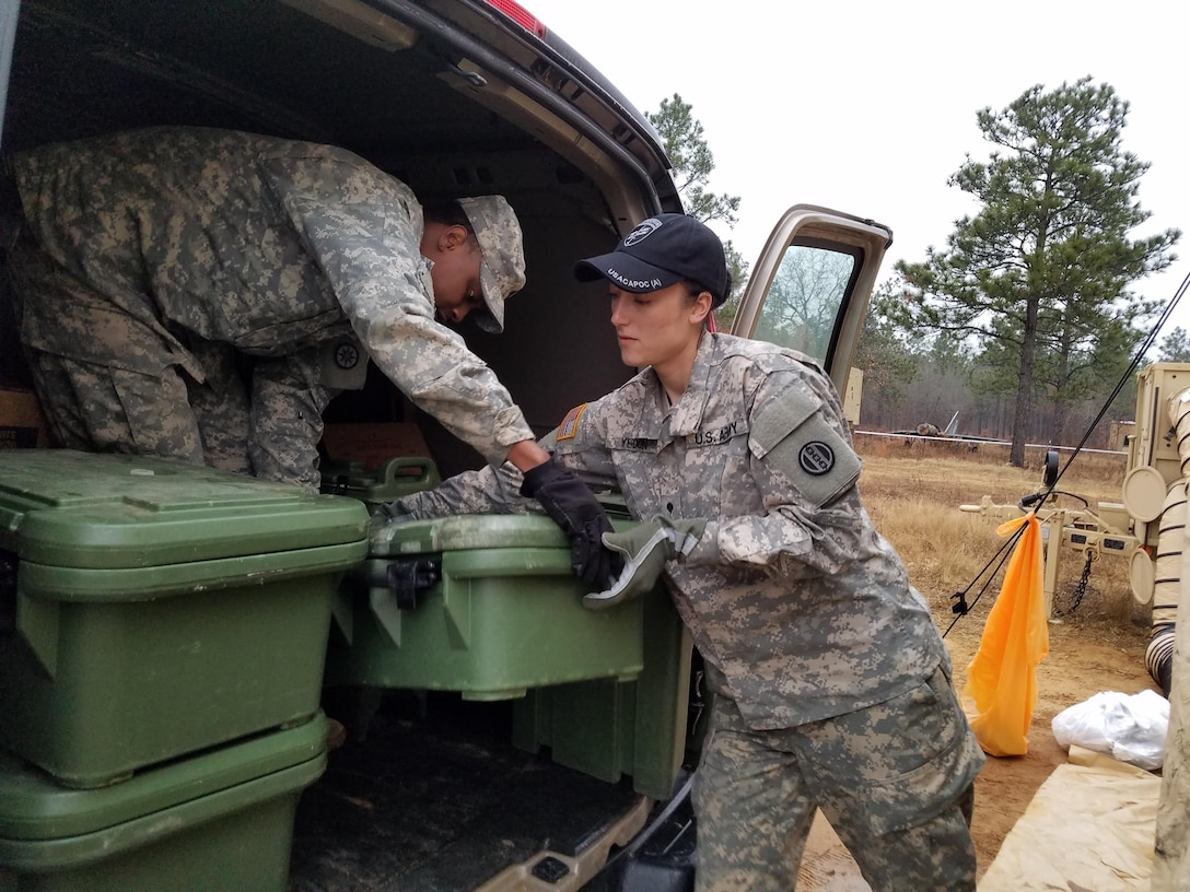 Spc. Savannah Yerdon (right), a culinary specialist assigned to 1018th Quartermaster Company in Schenectady, N.Y., and Sgt. Leroy McKinley (left), a heavy vehicle operator and culinary specialist assigned to 942nd Transportation Company in West Hartford, Conn., unload meal containers into the DFAC tent from their van in preparation for breakfast at Fort Bragg, N.C., Luzon Drop Zone on 12 Dec., 2016. Yerdon and McKinley was part of a six person food service crew who provided meal rations for hundreds of Soldiers during Operation Toy Drop XIX. (U.S. Army photo by Capt. Ebony Malloy)