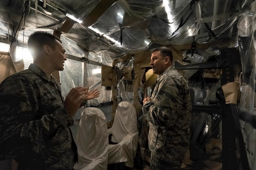 Senior Airman Peter Boyd, 628th Medical Group Bioenvironmental Engineering Flight biomedical maintenance technician, left, explains how the Transportation Isolation System works to Maj. Gen. Christopher J. Bence, U.S. Air Force Expeditionary Center commander, right, at the TIS hangar here, Dec. 15, 2016. While at Joint Base Charleston, Bence toured Team Charleston's facilities to get a first-hand look at joint operations.