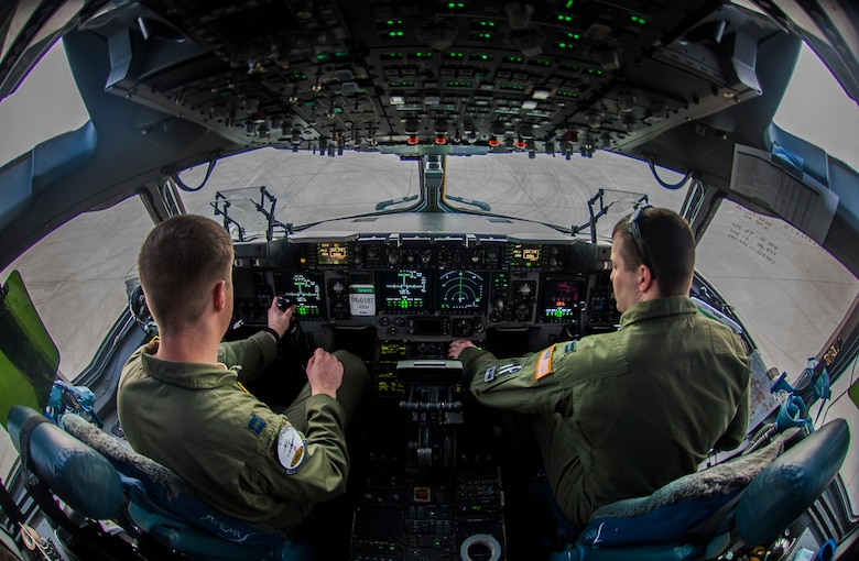 """Capt. Mike """"Havac"""" Gilpatrick, a pilot assigned to the 9th Airlift Squadron, Joint Base McGuire-Dix-Lakehurst, N.J., and Capt. Jason """"Brick"""" Sewell, a pilot assigned to the 43rd Operation Support Squadron, Pope Air Force Base, N.C., prepare a C-17 Globemaster III for take-off before a joint forcible entry exercise at Nellis Air Force Base, Nev., Dec. 10, 2016. JFEX is a U.S. Air Force Weapons School large-scale air mobility exercise in which participants plan and execute a complex air-land operation in a simulated contested battlefield. (U.S. Air Force photo by Airman 1st Class Kevin Tanenbaum)"""