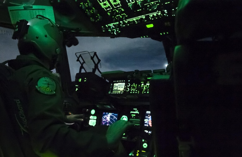 """Capt. Mike """"Havac"""" Gilpatrick, a pilot assigned to the 9th Airlift Squadron, flies a C-17 Globemaster III at night during a joint forcible entry exercise over the Nevada Test and Training Range, Dec. 10, 2016. Joint service exercises like the JFEX are integral to maintaining operational cohesiveness between the Air Force and the Army. (U.S. Air Force photo by Airman 1st Class Kevin Tanenbaum)"""