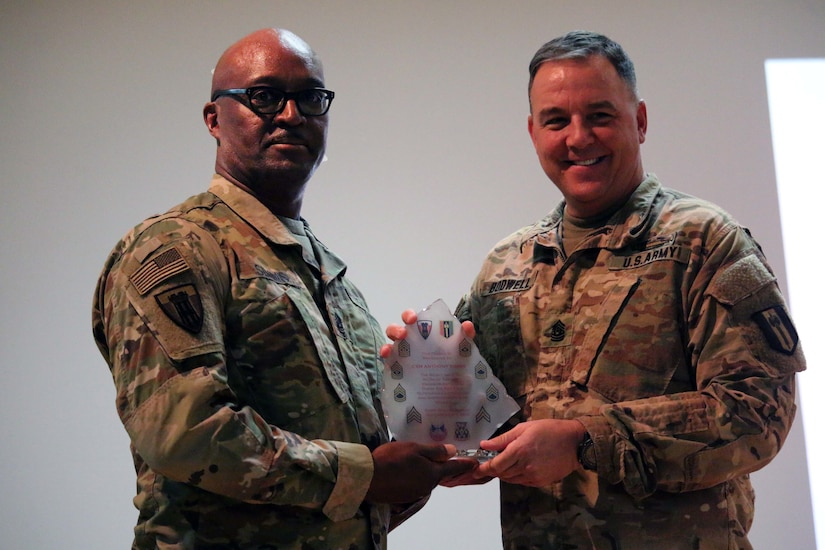 Command Sgt. Maj. Stephen M. Bodwell, 368th Eng. Bn. presents Command Sgt. Maj. Anthony Simms with a battalion award as a token of appreciation for his words of encouragement to Task Force Granite Soldiers participating in the Non-Commissioned Officer Induction Ceremony held at Camp Arifjan, Kuwait, Nov. 29, 2016. The ceremony consisted of approximately 106 Soldiers from 312th Eng. Co, 389th Eng. Co., 461st Eng. Co, 475th Eng. Co., Headquarters and Headquarters Co. and Forward Support Co. of 368th Eng. Bn. (U.S. Army photo by Capt. Maria Mengrone/Released)