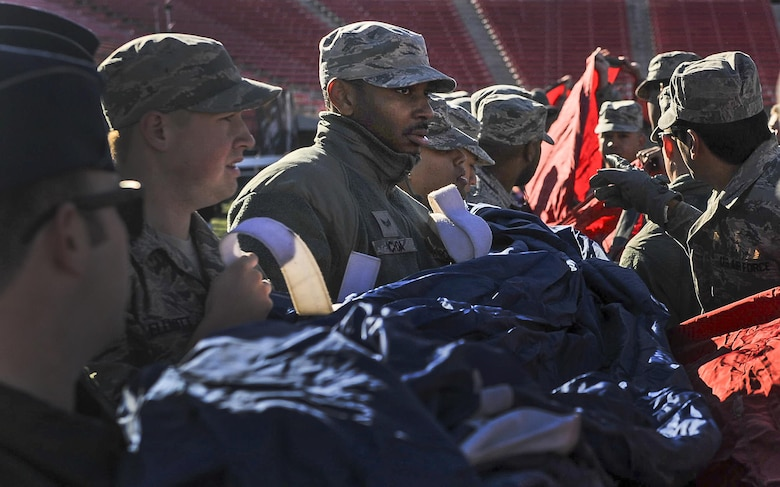 Airmen from Nellis and Creech Air Force Base unfold the American flag at Sam Boyd Stadium before the Las Vegas Bowl, Dec. 17, 2016. Over a 150 Airmen from Nellis and Creech AFB volunteered to hold the flag during the playing of the national anthem before the start of the bowl game. (U.S. Air Force photo by Airman 1st Class Kevin Tanenbaum/Released)