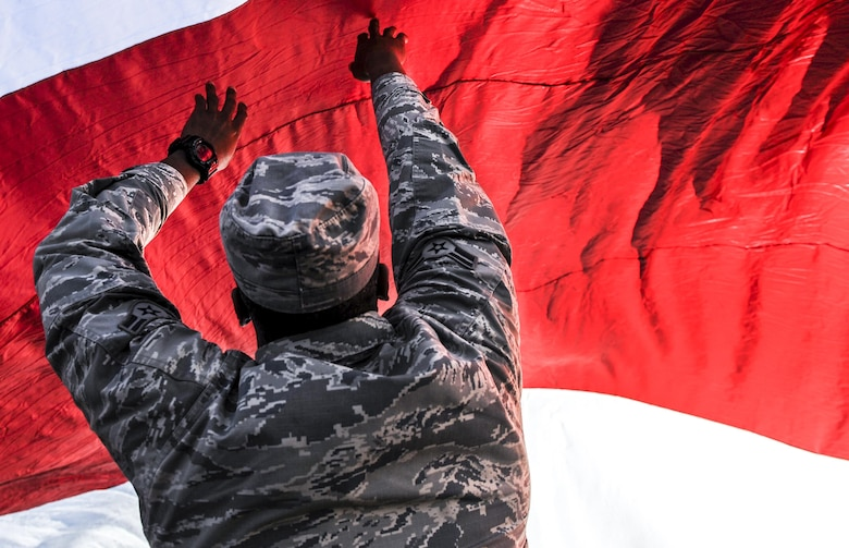 Airman 1st Class Corey Mitchell, 99th Air Base Wing Public Affairs broadcast engineer, holds up the American flag at Sam Boyd Stadium before the Las Vegas Bowl, Dec. 17, 2016. The Las Vegas Bowl featured the Houston Cougars facing off against the San Diego State Aztecs. (U.S. Air Force photo by Airman 1st Class Kevin Tanenbaum/Released)