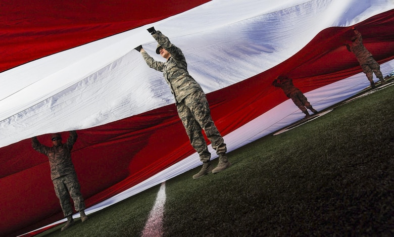 Airmen from Nellis and Creech Air Force Bases hold up the American flag at Sam Boyd & Nellis Creech Airmen raise American Flag during Las Vegas Bowl ...