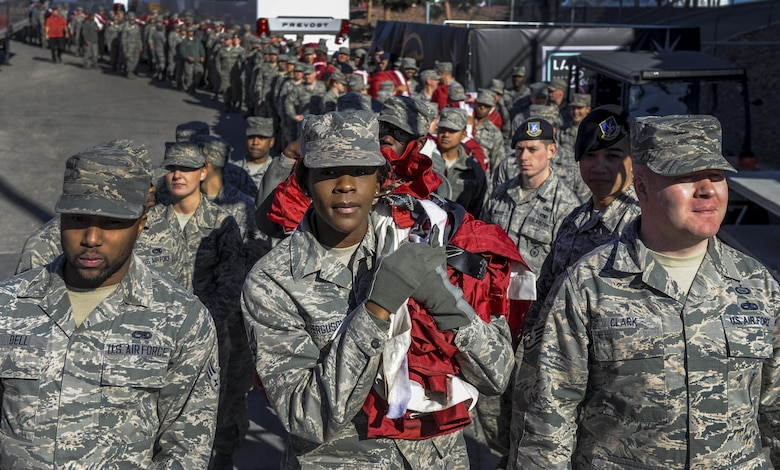 Airmen from Nellis and Creech Air Force Bases carry a large American flag before entering Sam Boyd Stadium during the Las Vegas Bowl, Dec. 17, 2016. The Airmen unveiled the flag before the game as the National Anthem was sung. (U.S. Air Force photo by Airman 1st Class Kevin Tanenbaum/Released)