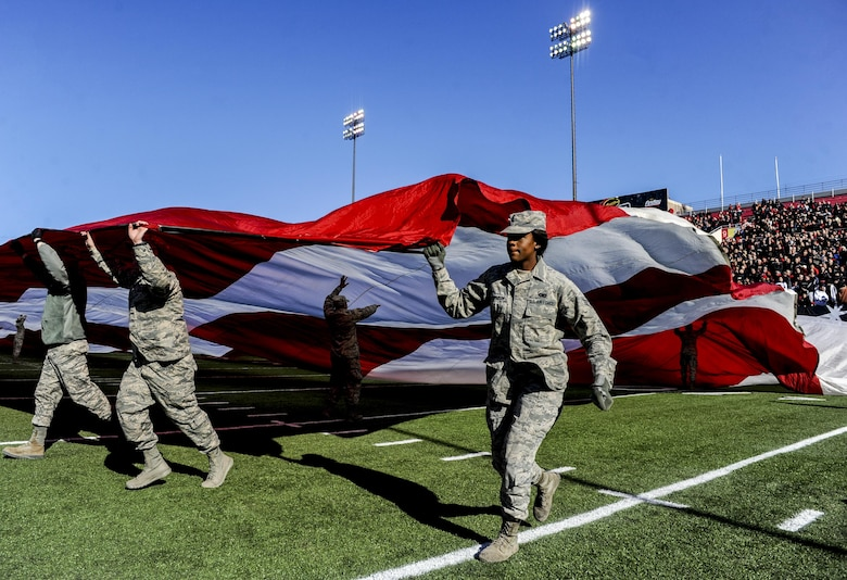 Airmen from Nellis and Creech Air Force Bases unveil the American Flag at Sam Boyd Stadium during the Las Vegas Bowl, Dec. 17, 2016. San Diego State senior Donnel Pumphrey earned the Rossi T. Ralenkotter Most Valuable Player Trophy by rushing for 115 yards on 19 carries during the game. (U.S. Air Force photo by Airman 1st Class Kevin Tanenbaum/Released)