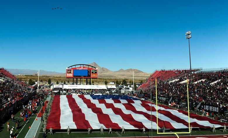 Four F-16 Fighting Falcons perform a fly-over as Airmen from Nellis and Creech Air Force Bases hold the American flag at Sam Boyd Stadium during the Las Vegas Bowl, Dec. 17, 2016. The F-16s flew over the stadium as the National Anthem played before the game began. (U.S. Air Force photo by Airman 1st Class Kevin Tanenbaum/Released)