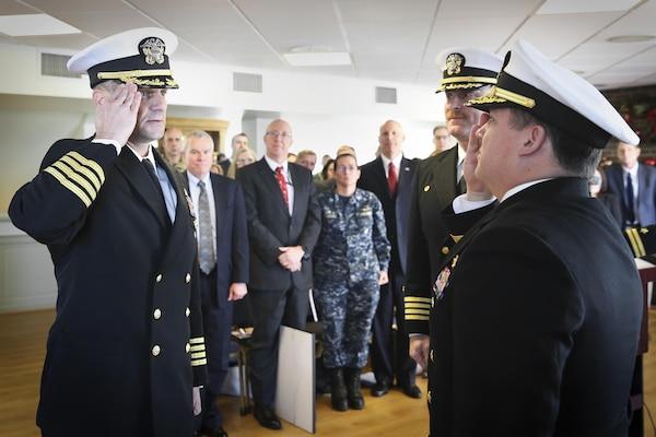 Capt. Scott Kraft salutes NSWC Commander Rear Adm. Tom Druggan after taking the helm of NSWC IHEODTD from Capt. Vincent Martinez at Indian Head, Dec. 15.