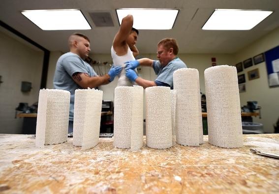Staff Sgt. Devin Rudd, (left) a student in the orthotics program, and Lawrence New, (right) a 59th Medical Wing orthotist and orthotics instructor, use plaster to create a mold for a body jacket orthoses at the Wilford Hall Ambulatory Surgical Center, Joint Base San Antonio-Lackland, Texas, Aug. 24, 2016. Staff Sgt. Kenneth Rivera, (center), is also a student in the orthotics program and served as the patient for the lesson. (U.S. Air Force photo/Staff Sgt. Jerilyn Quintanilla)