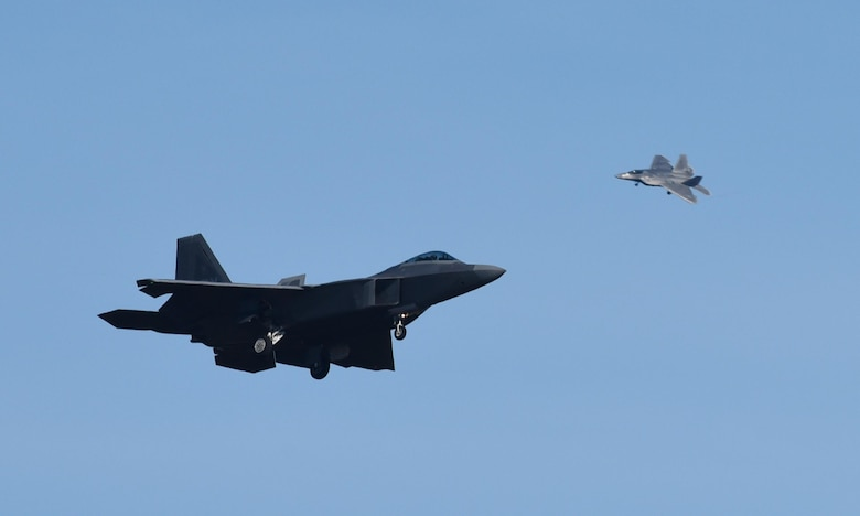 Two U.S. Air Force F-22 Raptors from Tyndall Air Force Base, Fla., fly over the base during Checkered Flag 17-1, Dec. 16, 2016. The integration training pilots receive during exercises like Checkered Flag ensure teams of different capabilities can seamlessly integrate and work together in a real-world combat situation utilizing fifth- and fourth-generation air assets. (U.S. Air Force photo by Staff Sgt. Alex Fox Echols III/Released)