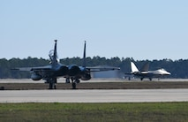 A U.S. Air Force F-15E Strike Eagle from Mountain Home Air Force Base, Idaho, sits at the ready while a Tyndall F-22 Raptor passes during Checkered Flag 17-1 at Tyndall Air Force Base, Fla., Dec. 16, 2016. During the exercise, fourth- and fifth-generation fighter pilots worked together to complete missions involving multiple airframes including the F-35A Lightning II, F-22, F-16CM Fighting Falcon, F-15E Strike Eagle, HH-60G Pave Hawk and  E-3 Sentry airframes. (U.S. Air Force photo by Staff Sergeant Alex Fox Echols III/Released)