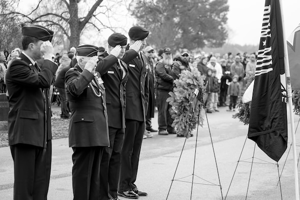 Airmen salute the Prisoner of War and Missing in Action flag during the Wreaths Across America ceremony, Dec. 17, 2016, at Evergreen Memorial Cemetery in Princeton, North Carolina. More than 50 Airmen from Seymour Johnson Air Force Base, North Carolina volunteered at the ceremony. (U.S. Air Force photo by Airman Shawna L. Keyes)