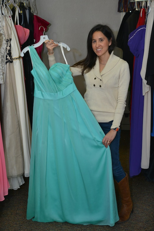 Yvonne Coombes, Operation Deploy Your Dress branch coordinator, displays a donated dress at Joint Base Langley-Eustis, Va., Dec. 20, 2016. Coombes, along with three other military spouses started ODYD to help military members and their spouses afford attending formal military events. (U.S. Air Force photo by Airman 1st Class Tristan Biese)