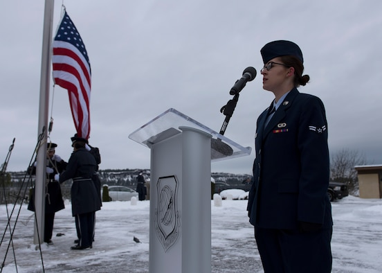 Airman 1st Class Sydney Silvester, 92nd Operations Support Squadron weather forecaster, sings the U.S. national anthem at the start of an official ceremony at Fort George Wright Cemetery Dec. 19, 2016, near Spokane, Washington. Service members braved freezing temperatures to honor the memory of the service members buried at the site. (U.S. Air Force Photo/Airman 1st Class Ryan Lackey)