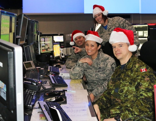 Eastern Air Defense Sector personnel conduct training in preparation for Santa tracking operations. Pictured from front to back, are: Sgt. Thomas Vance of the Royal Canadian Air Force, a member of EADS Canadian Detachment; and Master Sgt. Michelle Gagnon, Master Sgt. Lena Kryczkowski (standing) and Master Sgt. Shane Reid, all members of the New York Air National Guard's 224th Air Defense Squadron.