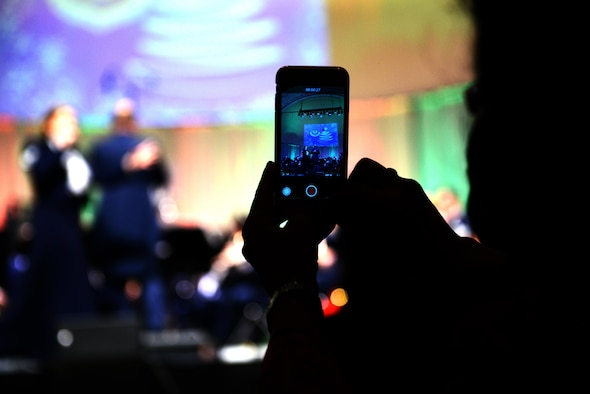 An audience member records a Christmas concert performed by the U.S. Air Forces Europe Band at Kaiserslautern, Germany. Dec. 16, 2016. Local nationals and U.S. military members attended the event, which aimed to bolster social and cultural ties between Americans and Germans.