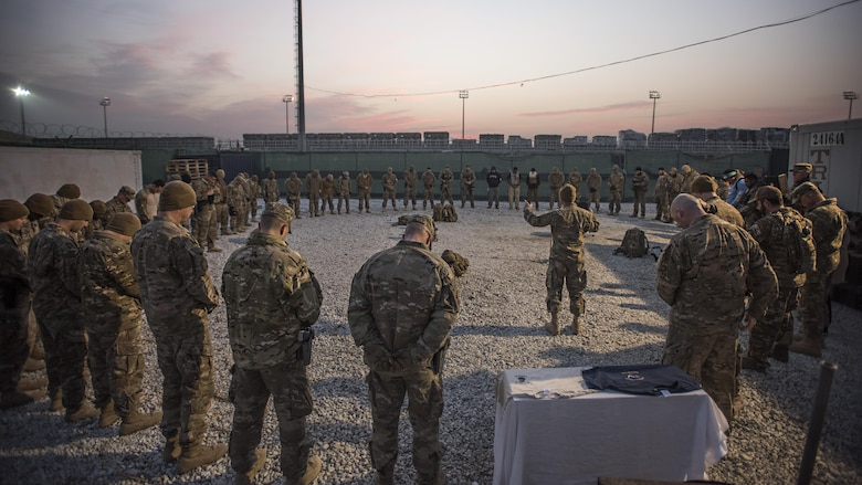 """Chaplain (Capt.) Benjamin Quintanilla, 455th Air Expeditionary Wing chaplain, says a prayer to a gathered group of Air Force Office of Special Investigations Expeditionary Detachment 2405 and 455th Expeditionary Security Forces Squadron members before a """"Ruck March to Remember"""" fallen comrades Dec. 21, 2016 at Bagram Airfield, Afghanistan. It is a tradition for Task Force Crimson members to gather in a prayer circle before going out on a mission outside the wire. (U.S. Air Force photo by Staff Sgt. Katherine Spessa)"""