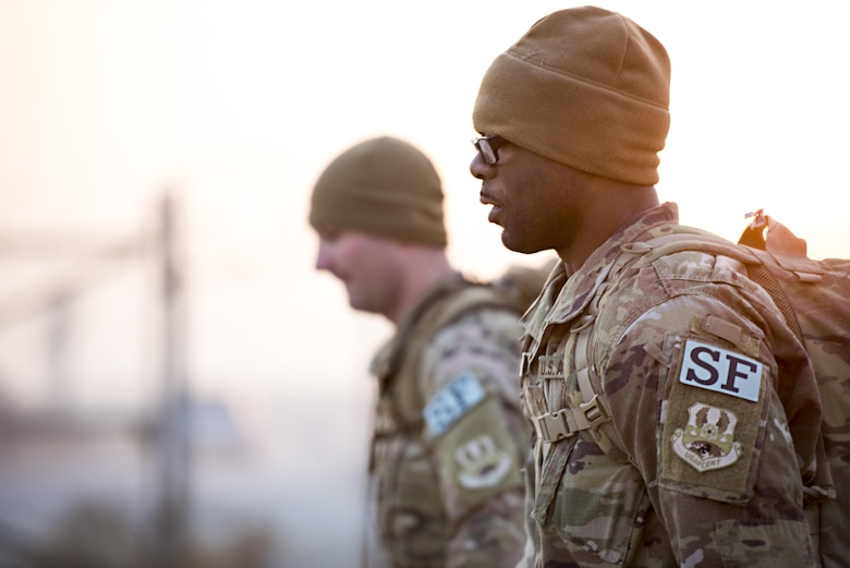 """One of the event's organizers, Staff Sgt. Jeffrey Tuscany and Operations NCOIC Tech. Sgt. Davon Muse, 455th Expeditionary Security Forces Squadron members, participate in a """"Ruck March to Remember"""" fallen comrades Dec. 21, 2016 at Bagram Airfield, Afghanistan. The ruck march was six miles long – one mile for each fallen Task Force Crimson Airman killed in an attack Dec. 21, 2015. (U.S. Air Force photo by Staff Sgt. Katherine Spessa)"""