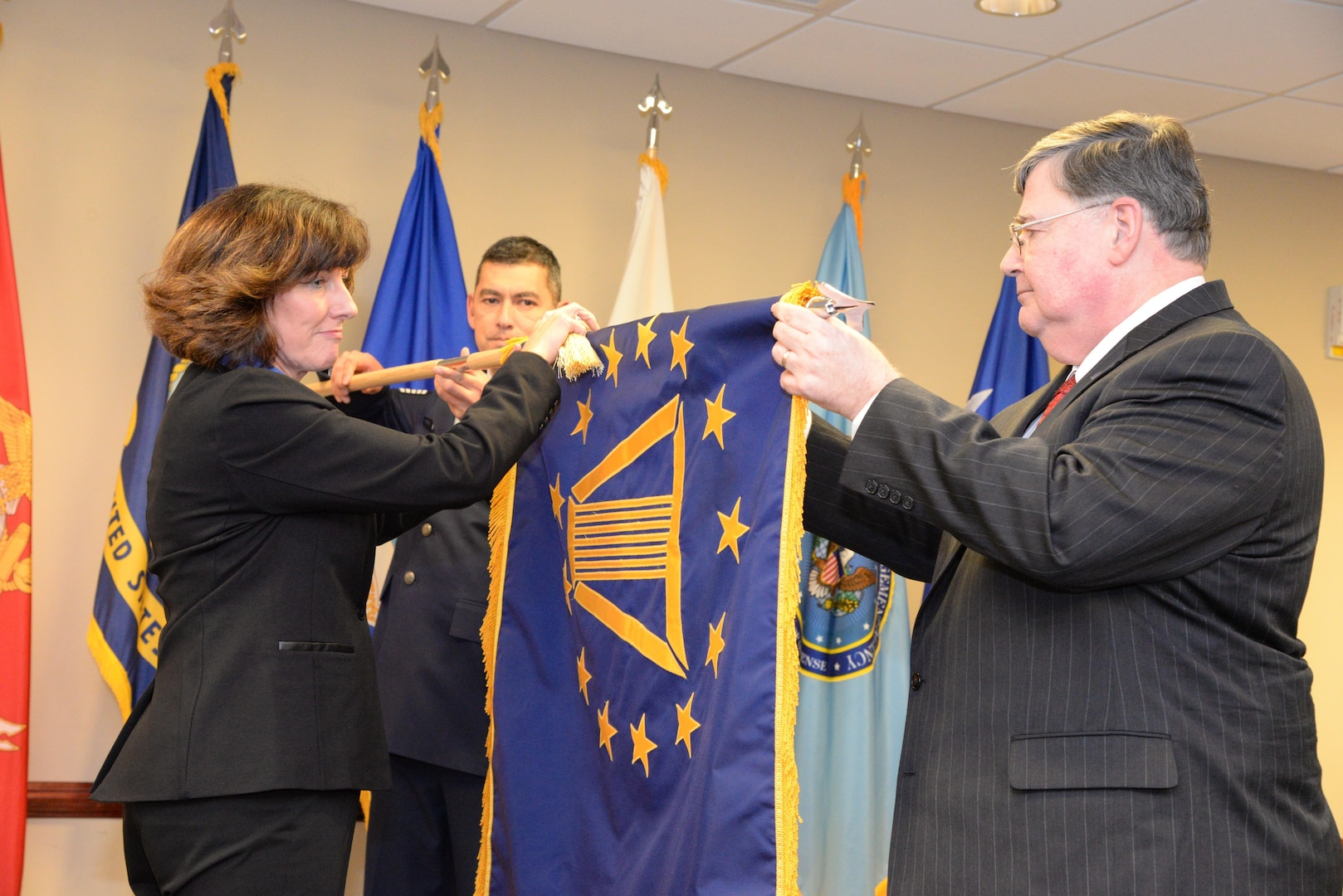 Pam Conklin, executive director of Defense Contract Management Agency Financial & Business Operations; and Timothy Callahan, executive director of DCMA Contract, ceremonially retire Jim Russell's Senior Executive Service flag at a Dec. 19 ceremony at Fort Lee, Virginia. Russell retired as the agency's deputy director after 36 years of federal service. (DCMA photo by Stephen Hickok)