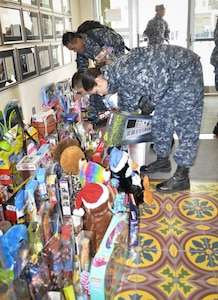 Students pick up toys in Anderson Hall at the Medical Education and Training Campus, or METC, on Joint Base San Antonio-Fort Sam Houston following a ceremony to wrap up METC's fifth annual toy drive. Anderson Hall was named after Petty Officer 3rd Class Christopher Anderson who was killed in action Dec. 4, 2006, in Ramadi, Iraq, while serving with the 1st Battalion, 6th Marines. Every year, Sailors at METC organize a toy drive in Anderson's honor to collect donations for Toys for Tots.