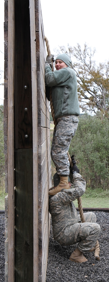 Spc. Victoria Lowery stands on her husband's – Spc. Chad Lowery – shoulder to climb over a wall obsticle during the confidence course at the first Guardian Challenge at Joint Base San Antonio-Camp Bullis Dec. 9. Both are assigned to Headquarters Support Company, Headquarters, Headquarters Battalion, U.S. Army North (Fifth Army) at JBSA-Fort Sam Houston.