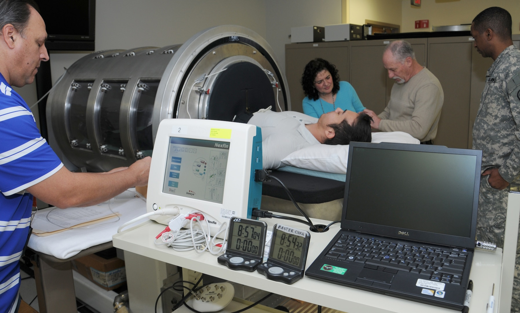 """(From left) Gary Muniz, Carmen Hinojosa-Laborde and Victor """"Vic"""" Convertino from the U.S. Army Institute of Surgical Research at Joint Base San Antonio-Fort Sam Houston place monitors on a volunteer in the lower body negative pressure chamber to collect physiological data as part of a research protocol as Lt. Col. Robert Carter (right) from USAISR looks on."""