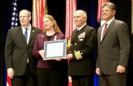 Mary Ann Spott (second from left), Ph.D., deputy director of the Joint Trauma System, or JTS, at the U.S. Army Institute of Surgical Research, or USAISR, at Joint Base San Antonio-Fort Sam Houston, is presented the Distinguished Civilian Service Award during an award ceremony at the Pentagon Nov. 6. Pictured from left to right with Spott are Bob Work, Deputy Secretary of Defense; Capt. (Dr.) Zsolt Stockinger, JTS director; and Michael Rhodes, director of administration and management, Office of the Secretary of Defense.
