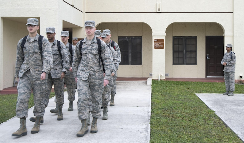 Master Sgt. Kelli Jackson (right), 558th Flying Training Squadron military training leader and superintendent, watches as a class of basic sensor operator technical training students march to class at Joint Base San Antonio-Randolph Dec. 14, 2016. An MTLs basic duty is to help non-prior service Airmen transition to military life, continuing the training they received at basic military training. (U.S. Air Force photo illustration by Airman 1st Class Lauren Parsons/Released)