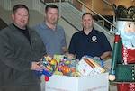 "DLA Energy employees and retired Marines, from left to right, Dan Martineau, Richard ""Tony"" Rabak and Jason Hayungs place new, unwrapped toys in the Toys for Tots drop boxes at Fort Belvoir, Virginia, Dec. 15."