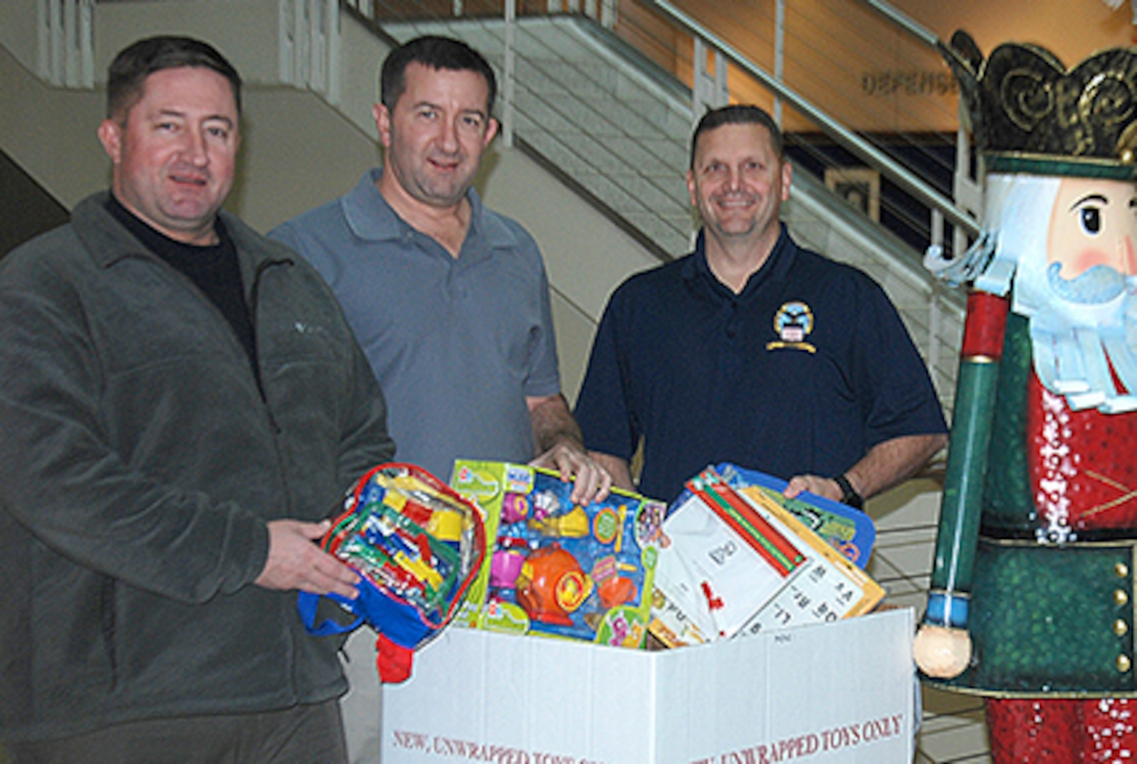 """DLA Energy employees and retired Marines, from left to right, Dan Martineau, Richard """"Tony"""" Rabak and Jason Hayungs place new, unwrapped toys in the Toys for Tots drop boxes at Fort Belvoir, Virginia, Dec. 15."""
