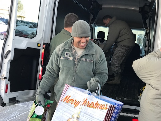 Capt. William-Joseph Mojica, 934th Airlift Wing public affairs officer, unloads gifts at the Minnesota Veteran's Home Dec. 15.