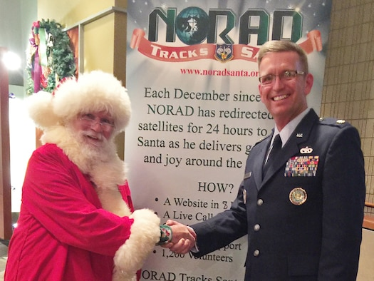 Lt. Col. Karl Fruendt shakes hands with Santa Claus at a NORAD Tracks Santa event. Lt. Col. Karl Fruendt is the voice behind the English-language videos on the NORAD Tracks Santa website and is also part of local holiday performances, narrating the history of the NORAD-run service. (Courtesy photo)