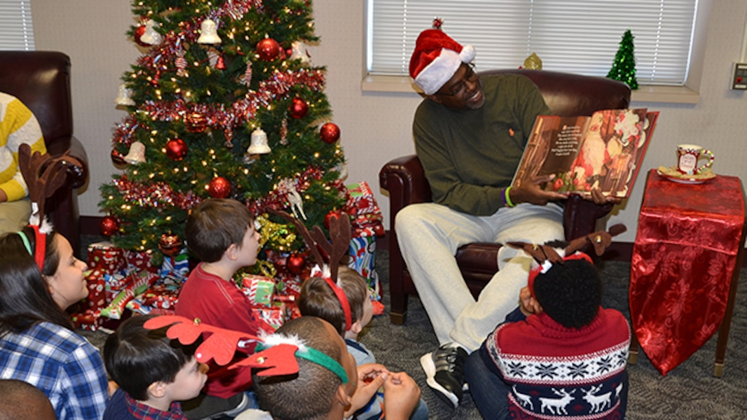 Defense Logistics Agency Aviation Customer Operations Mapping employee, Kevin Bettis, division chief, reads to children of Mapping employees Dec. 20, 2016. The children came to the installation to make Christmas cards to attach to gifts purchased by employees. The gifts are being donated to the children who are patients at Children's Hospital of Richmond at Virginia Commonwealth University.
