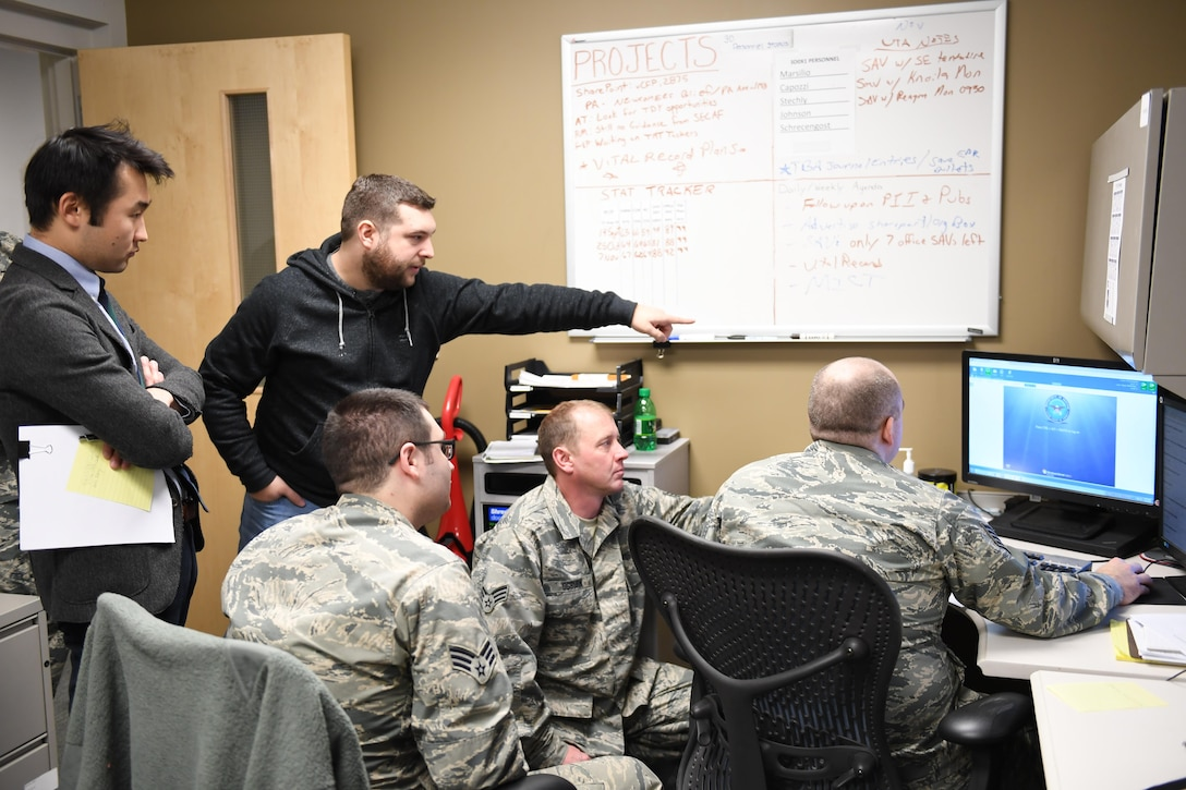 Luke Osterritter, cyber security engineer with Carnegie Mellon University, and Jerry Guo, PhD student with the Tepper School of Business, assist Airmen during exercise Cyber Tepper, a cyber exercise hosted by Carnegie Mellon University, at the Pittsburgh International Airport Air Reserve Station, Pennsylvania, Nov. 4, 2016. The exercise was part of Guo's study to determine if teams that rely less on procedures will perform better in dynamic environments. (U.S. Air Force photo by Senior Airman Beth Kobily)