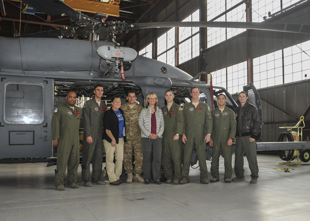 Carol Powell and Ronda Ramsier take a photo with 58th Special Operation Wing and 512th Rescue Squadron members in front of one of the HH-60G Pavehawks used to perform a search-and-rescue for them. Powell and Ramsier  became stranded for 36 hours with their two llamas during an evening hike early August. The hikers returned to Kirtland Dec. 12 to thank the members of the units who rescued them.