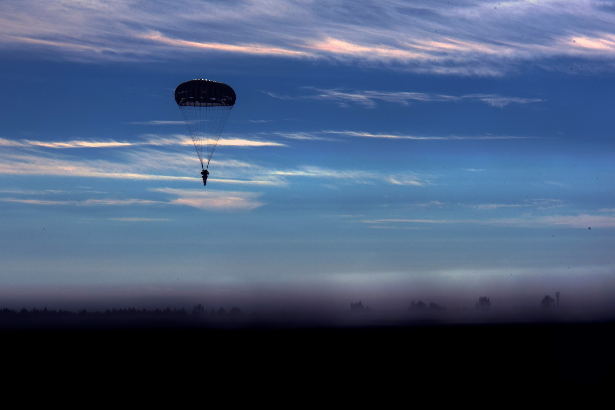 A U.S. Army airborne specialist parachutes in the sky after a sustained jump during the 19th Annual Randy Oler Memorial Operation Toy Drop, Dec. 14, 2016, at Luzon Drop Zone, Camp Mackall, N.C. The OTP tradition was established in 1998 by the late U.S. Army Reserve Staff Sgt. Randy Oler, Civil Affairs and Psychological Operations Command soldier with 1,200 soldiers participating and has grown into a multinational exercise with 4,000 paratroopers. (U.S. Air Force photo by Airman 1st Class Greg Nash)