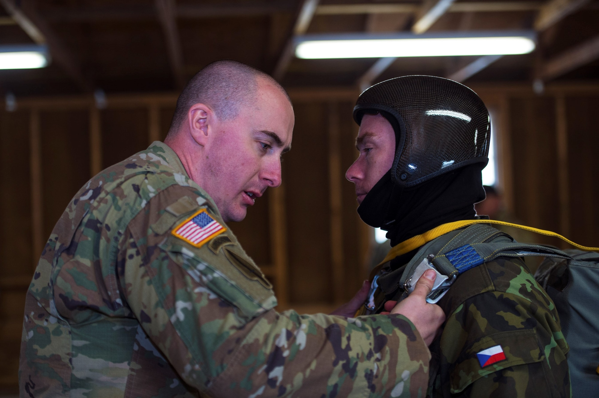 U.S. Army Staff Sgt. Nathaniel Bier, 301st Psychological Operations Company airborne specialist, left, inspects Czech Republic army warrant officer Miroslav Kloupar's parachute ensemble during the 19th Annual Randy Oler Memorial Operation Toy Drop, Dec. 16, 2016, at Mackall Army Air Field, N.C. OTD is the world's largest annual multinational airborne exercise which included 120 jumpmasters and 4,000 paratroopers during this year's event. (U.S. Air Force photo by Airman 1st Class Greg Nash)