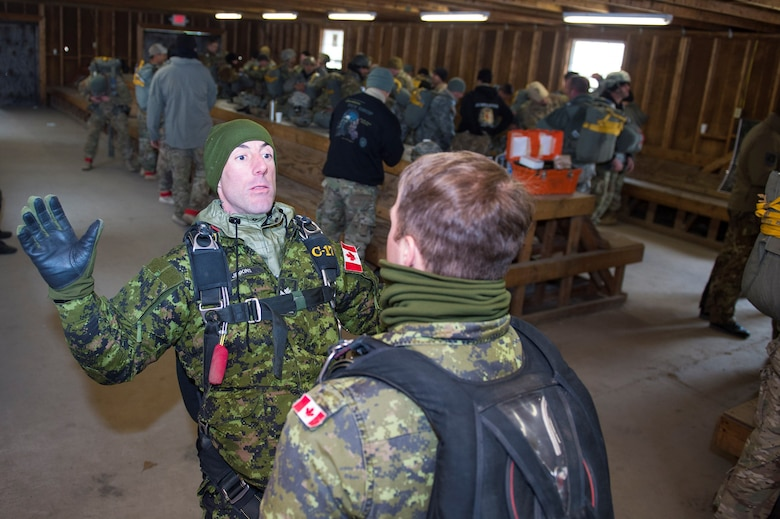 Sergeant Daniel Jenkins, Canadian army Advanced Warfare Center parachute instructor, shows Master Corporal Joey Miller, fellow CAAWC parachute instructor, exiting strategies to employ after flight during the 19th Annual Randy Oler Memorial Operation Toy Drop, Dec. 16, 2016, at Mackall Army Air Field, N.C. In addition to Canada, the nations of Botswana, Czech Republic, Germany, Italy, the Netherlands, Poland, and Singapore also participated. (U.S. Air Force photo by Airman 1st Class Greg Nash)