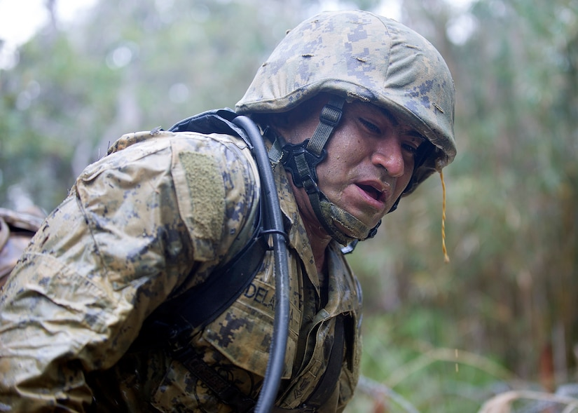Navy Petty Officer 2nd Class Oscar C. Delarosa gasps for air after crawling through muddy trenches during a 3.8-mile obstacle course at the Jungle Warfare Training Center in Okinawa, Japan, Jan. 12, 2016. Delarosa is assigned to Naval Mobile Construction Battalion 3. Navy photo by Petty Officer 1st Class Michael Gomez