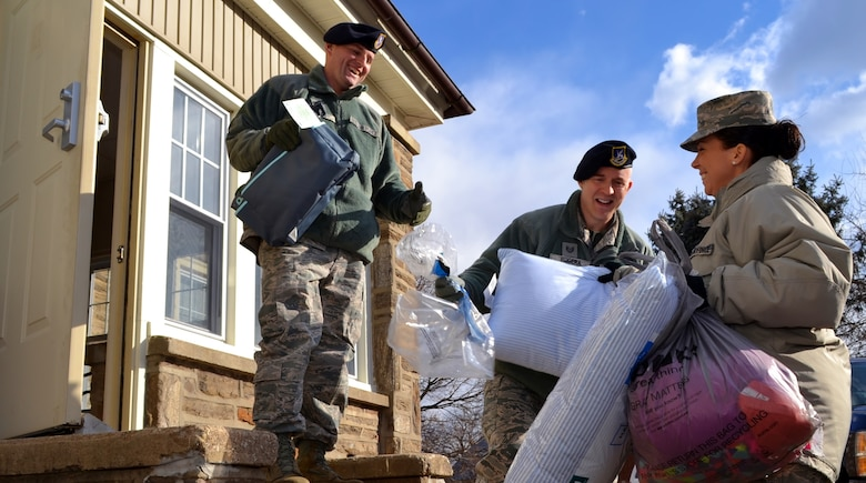 On right, Senior Master Sgt. Lauren Paul, 111th Force Support Squadron service superintendent, holds armfuls of donated items to pass off to 111th Security Forces Squadron members during the delivery to a local child services facility in Warminster, Pennsylvania, Dec. 15, 2016. Members of the Wing have conducted The Angel Tree holiday donation drive for more than 20 years. (U.S. Air National Guard photo by Tech. Sgt. Andria Allmond)