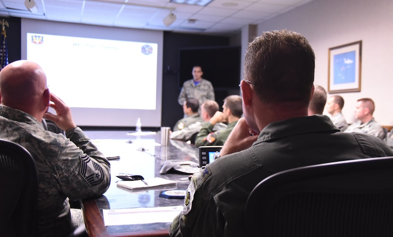 U.S. Air Force Col. Lance Wilkins, 53rd Weapon Evaluations Group commander, listens to Airmen briefing him in the 53rd WEG conference room Dec. 16, 2016. The initiative is meant to facilitate dialog between different squadrons within the 53rd WEG, who may or may not have had face-to-face interaction, to come up with plausible solutions for problems they may face. (U.S. Air Force photo by Senior Airman Solomon Cook/Released)